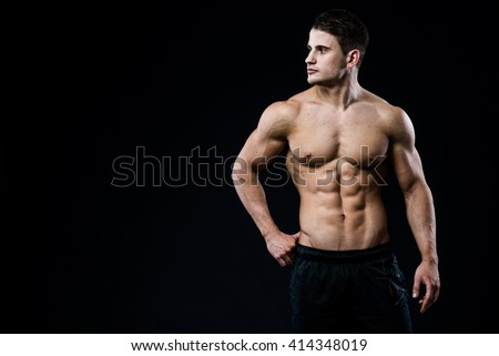 Young and fit male model posing his muscles looking to the left isolated on black background with copyspace. Man showing his six pack abs on dark background - stock photo
