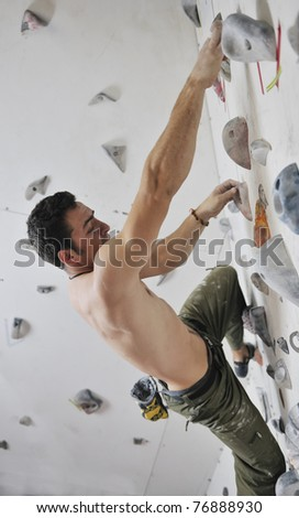 young and fit man exercise free mountain climbing on indoor practice wall - stock photo