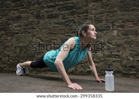 Young and fit sporty woman doing push-ups during outdoor training session. Action and healthy lifestyle concept. - stock photo