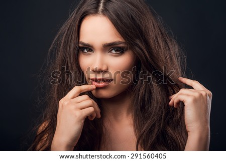 Young and flirty. Beautiful young shirtless woman touching her lips and looking at camera while standing against black background   - stock photo