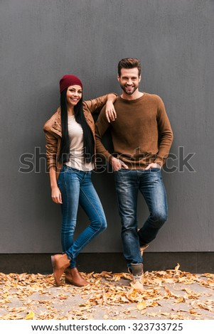 Young and free. Beautiful young couple bonding to each other and smiling while leaning at the grey wall with fallen leaves laying around them - stock photo