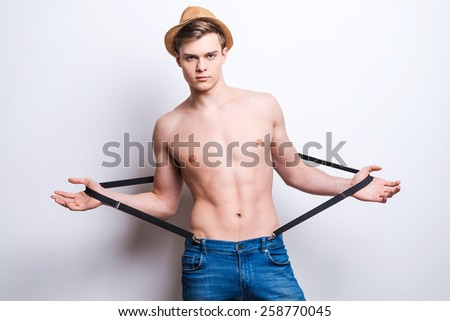 Young and free. Handsome young hipster pulling suspenders while standing against grey background  - stock photo