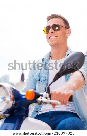 Young and free. Low angle view of handsome young man in sunglasses riding scooter along the street and smiling  - stock photo