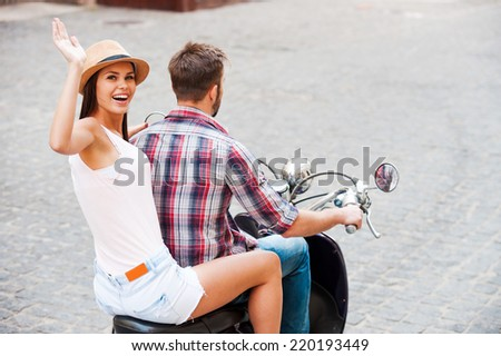 Young and free. Rear view of beautiful young couple riding scooter together while beautiful woman looking over shoulder and waving to you with smile - stock photo