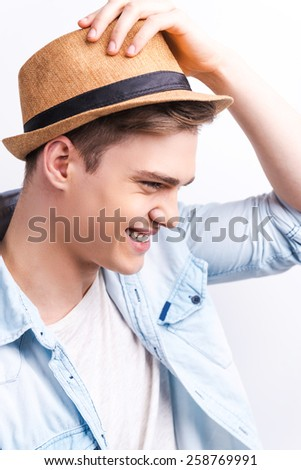 Young and free. Side view of  handsome young man smiling and adjusting his hat while standing against grey background.  - stock photo