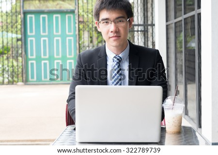 young and handsome asian business man using his computer in a outdoor coffee shop looking straight (selective focus technique applied) - stock photo