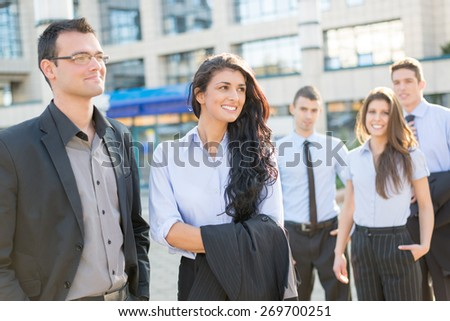 Young and handsome businessman and businesswoman standing with his team front of office building and smiling. - stock photo