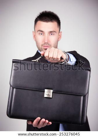 Young and handsome businessman giving a briefcase. Vignetting - stock photo