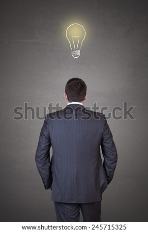 Young and handsome businessman thinking in front of light idea bulb concept - stock photo