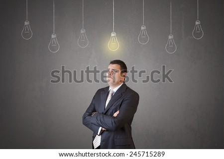 Young and handsome businessman thinking in front of light idea bulbs concept - stock photo