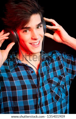 Young and handsome dj with headphones - Disco light effect - stock photo