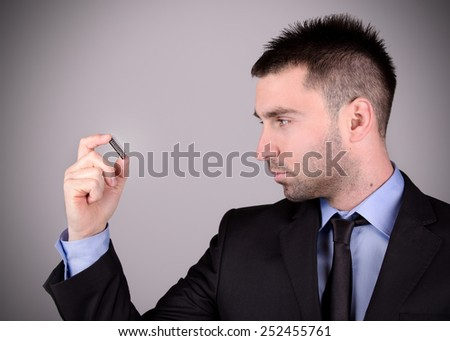 Young and handsome electronic engineer holding computer microchip, vignetting. - stock photo