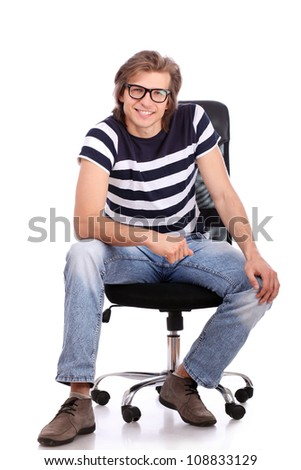 Young and handsome guy sitting on the chair  over white backround - stock photo