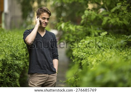 Young and handsome guy talking on mobile phone outdoors.