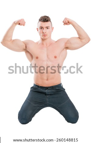 Young and handsome male model on his knees flexing muscular strong arms - stock photo