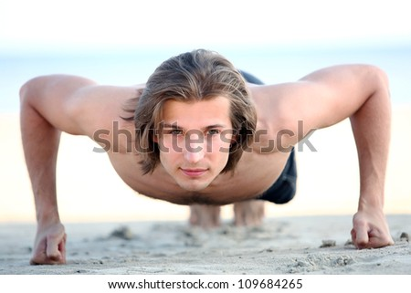 Young and handsome man doing push ups on the beach