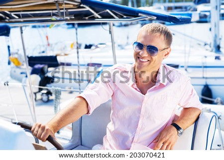 Young and handsome man on luxury yacht - stock photo