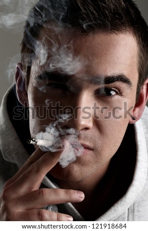 Young and handsome man smoking cigarette