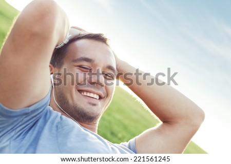 young and handsome man with earplugs lying in the park and listening music - stock photo