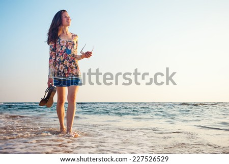 young and handsome woman looking far away near the ocean - stock photo