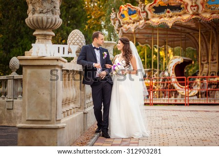 Young and happy bride and groom in wedding clothes with sign Family
