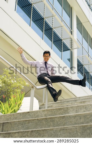 Young and happy chinese businessman sliding downstairs on rails of office staircase. The man enjoys his new promotion at job - stock photo
