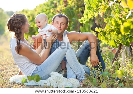 Young and happy family get stroll in the park - stock photo