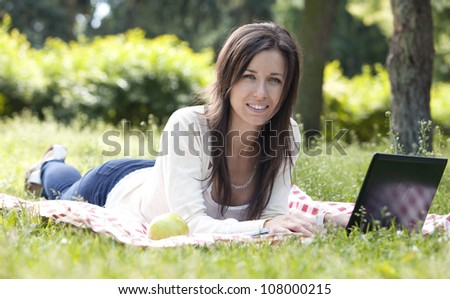 Young and happy girl with laptop in the park