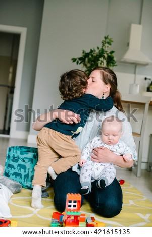 Young and happy mother embracing with their young children on the floor at home. Children laugh. Concept of family. Mother kissing her son - stock photo