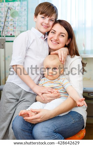 Young and happy mother hugs her two beautiful children. Sitting on chair in children room at home - stock photo