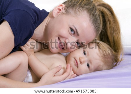 Young and happy mother playing with her little girl