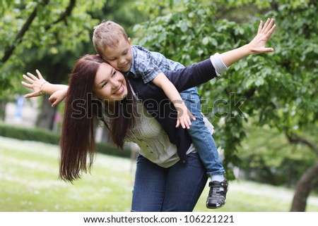 Young and happy mother with her son in the park - stock photo