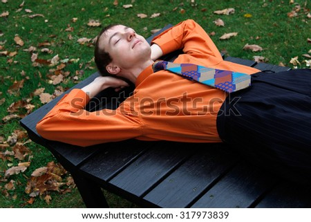 Young and happy office employee sleeping in chaise-lounge / deck chair / daybed outdoors after lunch. An image in favor of siesta for a concept of successful business or modern lifestyle.