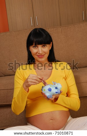 Young and happy pregnant woman holding a piggy bank,