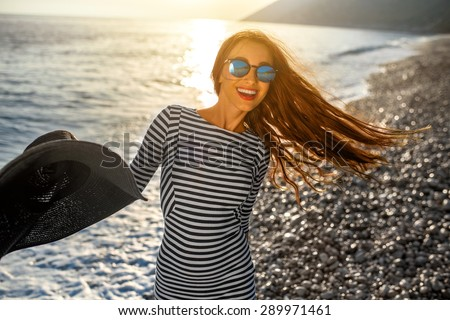Young and happy woman in stripped dress jumping with a hat in the hand on the beach on sunset against the sun. Feeling free and joyful - stock photo