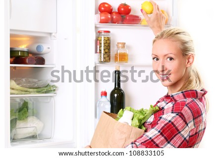 Young and happy woman is putting a food into the fridge - stock photo