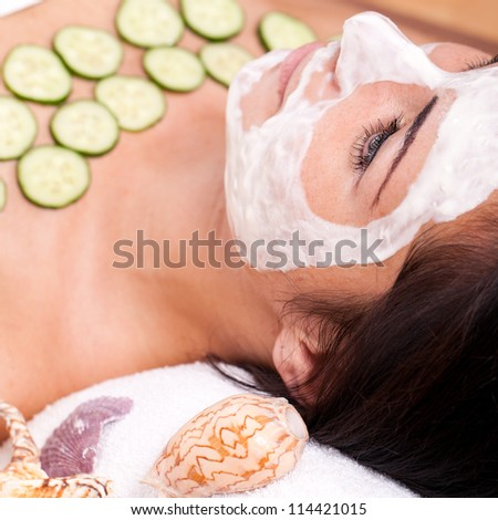 Young and happy woman relaxing with facial mask
