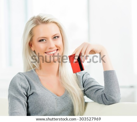Young and happy woman with a credit card. Online shopping concept. - stock photo