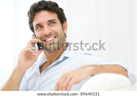 Young and healthy man smiling and talking on smart phone at home - stock photo