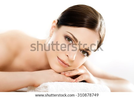 Young and healthy woman in spa salon isolated on white - stock photo