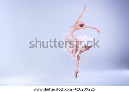 Young and incredibly beautiful ballerina is posing and dancing in a white studio full of light. The photo greatly reflects the incomparable beauty of a classical ballet art. - stock photo