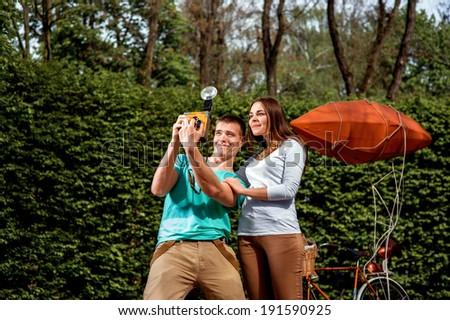 Young and joyful couple having fun and photographing with old photo camera in the park with bicycle on background - stock photo