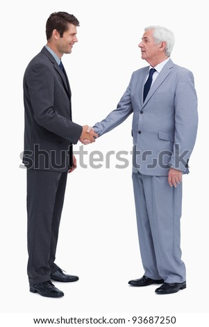 Young and mature businessmen shaking hands against a white background - stock photo