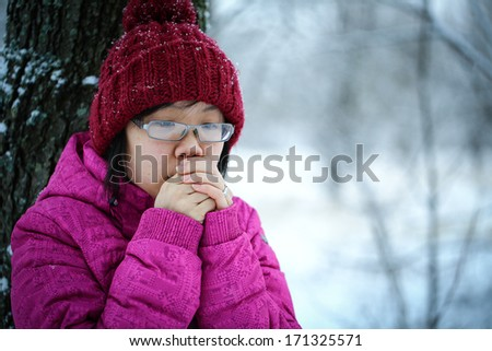 Young and moody asian girl with a pink jacket leaning against a tree in the winter
