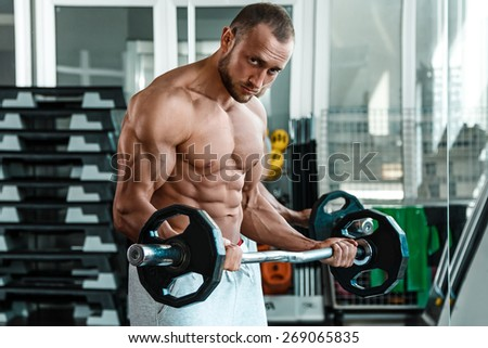 Young and muscular man during workout in the gym - stock photo