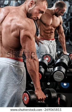Young and muscular man in the gym - stock photo