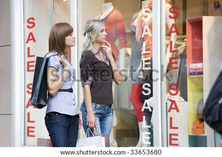 young and nice women in front of a window shop in act to decide what to buy - stock photo