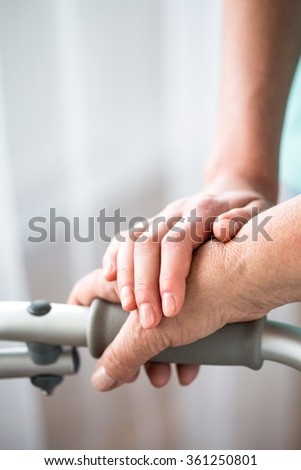 Young and old hand on walking frame - stock photo