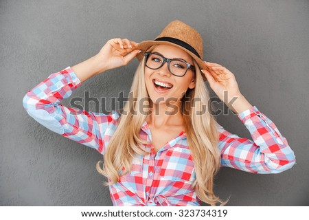 Young and playful. Cheerful young woman adjusting her headwear and looking at camera while standing against grey background - stock photo