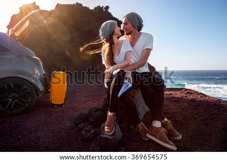 Young and pretty couple dressed alike kissing near the car on the rocky coast on the sunset